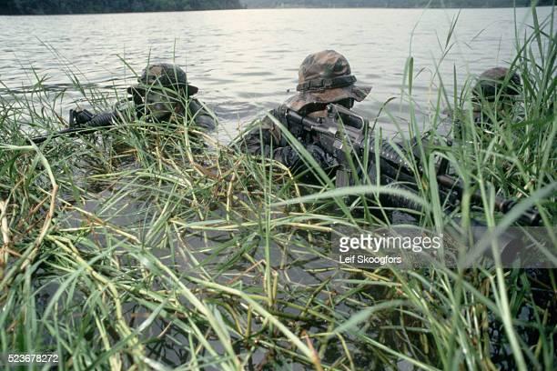 navy seals camouflaged in a river - navy seals de los estados unidos fotografías e imágenes de stock