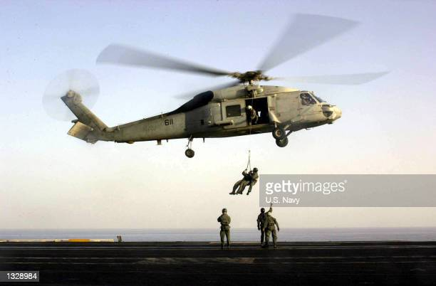 """Navy SEALs train with an SH-60F """"Seahawk"""" helicopter October 18, 2001 on the flight deck of USS Enterprise. Aircraft from the Enterprise are being..."""