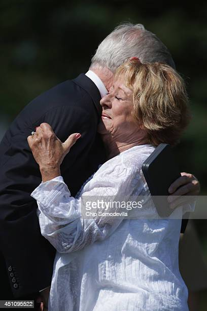 S Navy Secretary Ray Mabus embraces Judy Johnson after giving her the Navy Distinguished Civilian Service Medal with Valor on behalf of her husband...