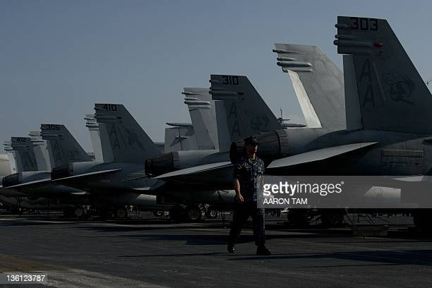 Navy serviceman walks past F/A18 Hornet warplanes on the flight deck of the USS Carl Vinson a US nuclear powered aircraft carrier anchored in Hong...