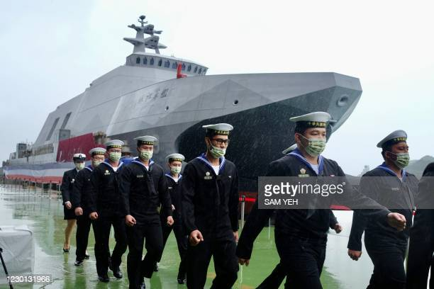 Navy soldiers walk past a indigenous Tuo Chiang class corvette missile ship during an official ceremony at a shipyard in Suao, in Yilan county,...