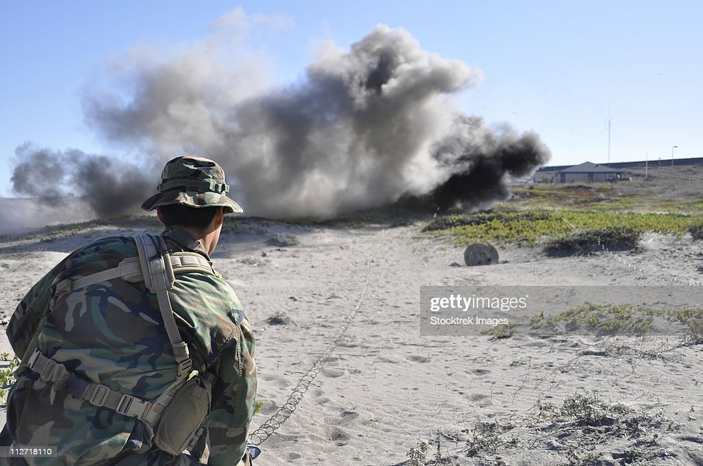 A U.S. Navy student in basic underwater demolition/SEAL training detonates a standard charge. : Stock Photo