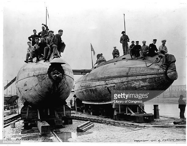 Navy submarine crewmen sit on the bows of the drydocked submarines USS Porpoise and USS Shark