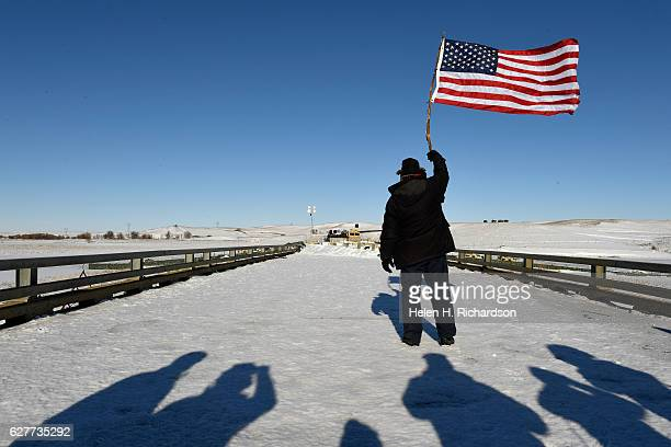 Navy veteran John Gutekanst holds an American flag towards the police barricade on a bridge near Oceti Sakowin Camp on the edge of the Standing Rock...