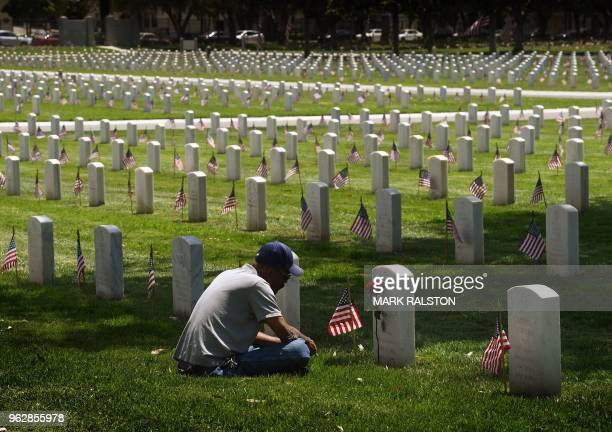 Navy veteran Richard Jones prays before the grave of his friend James McDermott at the Los Angeles National Military Cemetery two days prior to...