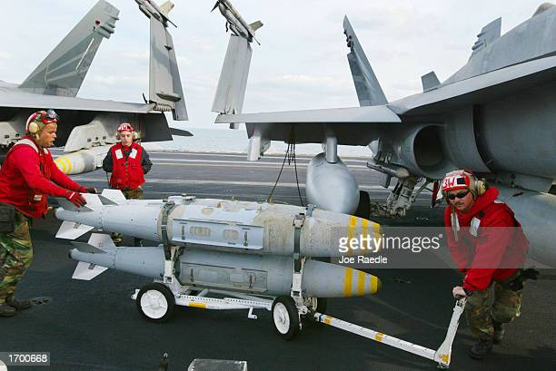 S Navy weapons ordinance men wheel bombs to fighter planes on the deck of the USS Constellation December 24 2002 in the Persian Gulf The war planes...