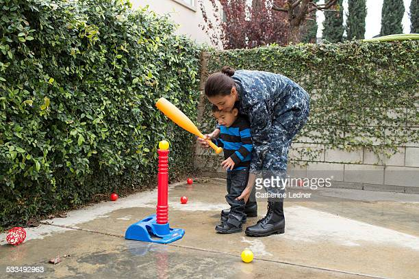 navy woman teaching young son tball - baseball mom stock pictures, royalty-free photos & images