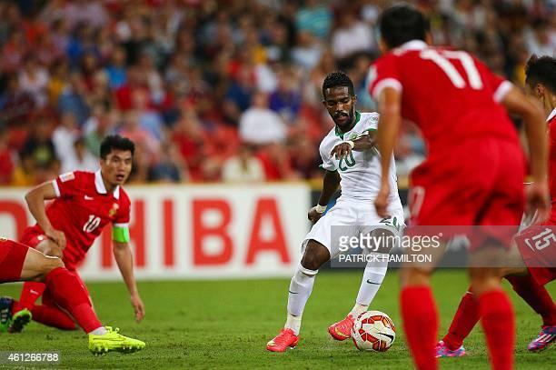 Nawaf Alabid of Saudi Arabia beats the defence of captain Zheng Zhi and Wu Xi during the first round Asian Cup football match between China and Saudi...