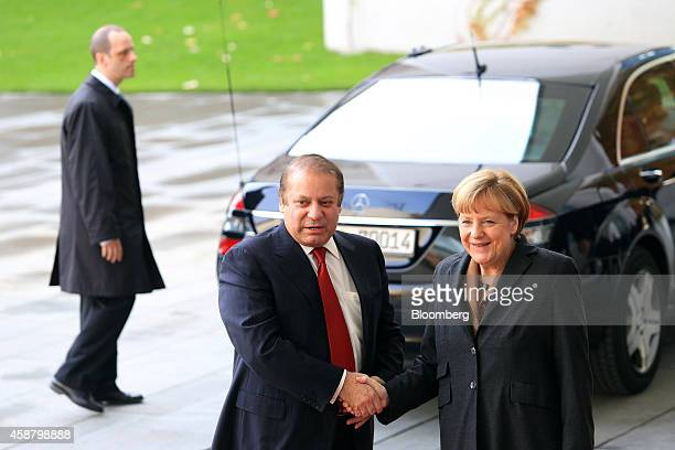 Nawaz Sharif Pakistan's prime minister center poses for a photograph with Angela Merkel Germany's chancellor ahead of a news conference at the...