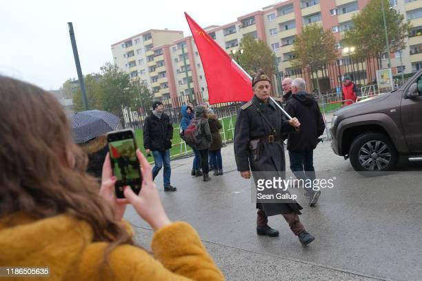 Naydencho Naydenov who describes himself as a bornagain communist wears an old Soviet military uniform and carries a Soviet flag along an area where...