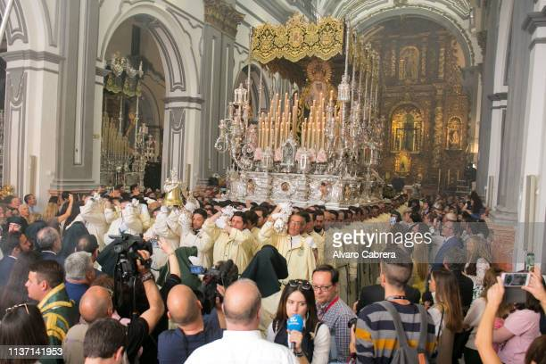 Nazarenes carry the float of the icon of The Virgin of Lágrimas y Favores as they take part in the Lagrimas y Favores brotherhood's Palm Sunday...