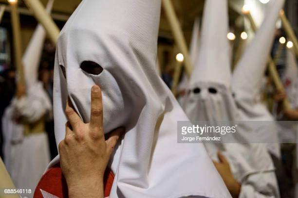 Nazarenos participating in a religious procession with the traditional robes and hoods and carrying candles during Semana Santa in Seville