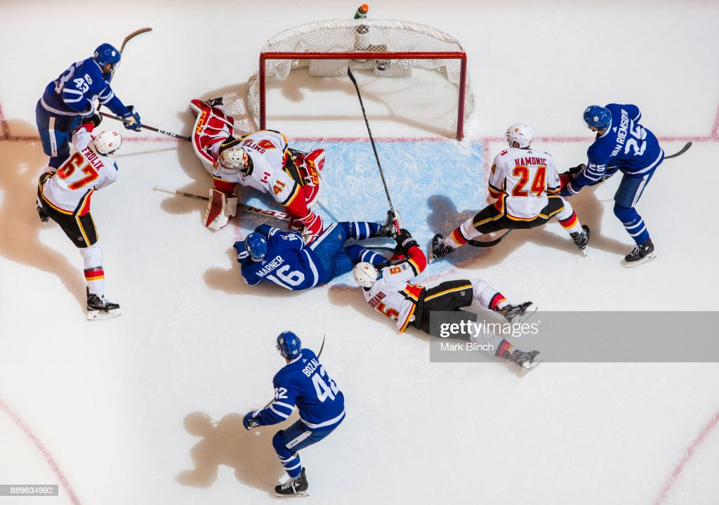 Nazem Kadri #43, Mitchell Marner #16, Nazem Kadri #43, James van Riemsdyk #25 of the Toronto Maple Leafs go to the net against Mike Smith #41, Michael Frolik #67, Mark Giordano #5, and Travis Hamonic #24 of the Calgary Flames during the first period at the Air Canada Centre on December 6, 2017 in Toronto, Ontario, Canada.