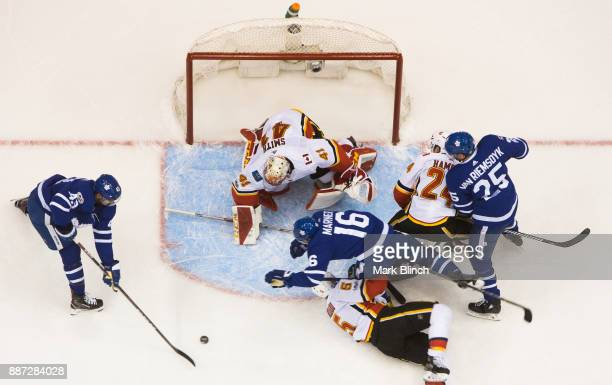 Nazem Kadri of the Toronto Maple Leafs and Mike Smith of the Calgary Flames watch the puck as James van Riemsdyk and Mitch Marner battle with Mark...