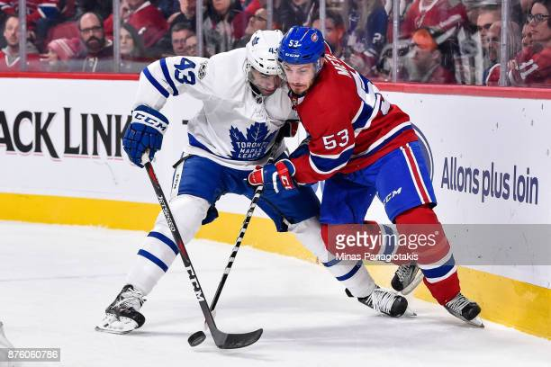 Nazem Kadri of the Toronto Maple Leafs and Victor Mete of the Montreal Canadiens battle for the puck during the NHL game at the Bell Centre on...