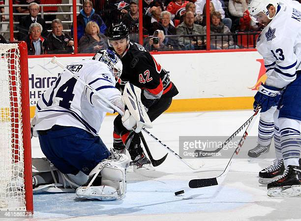 Nazem Kadri of the Toronto Maple Leafs attempts to clear the puck as James Reimer defends the net against Brett Sutter of the Carolina Hurricanes...