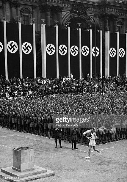Nazi banners hang around the edges of a square where crowds gather to watch the lighting of the Olympic flame Berlin 1936