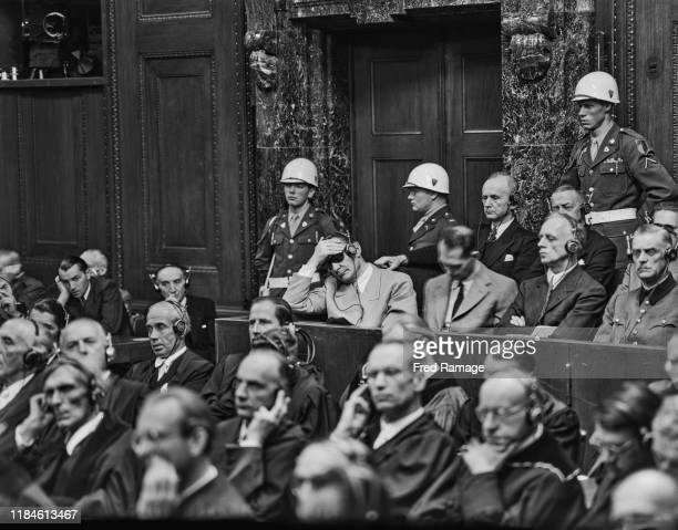 Nazi defendant Hermann Goering in the dock behind the defence counsel, under guard in Room 600 at the Palace of Justice in Nuremberg during legal...