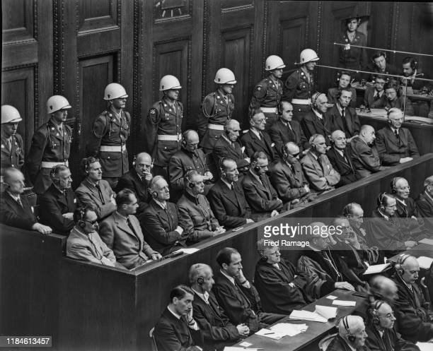 Nazi Defendants in the dock under guard in Room 600 at the Palace of Justice in Nuremberg during legal proceedings against leading Nazi figures for...