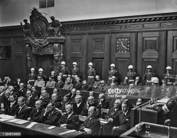 Nazi Defendants sit in the dock behind their legal counsel under guard in Room 600 at the Palace of Justice in Nuremberg during legal proceedings...