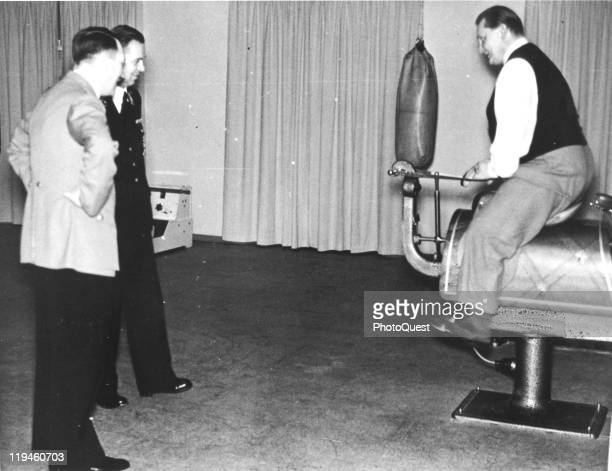 Nazi dictator Adolf Hitler and an unidentified officer Nazi official watch as Hermann Goering demonstrates an exercise horse in the home gymnasium of...