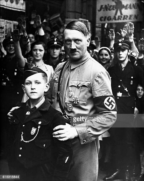 Nazi dictator Adolph Hitler poses with a young member of the Nazi Youth