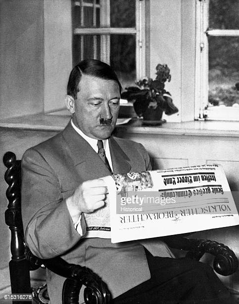 Nazi dictator Adolph Hitler reads the front page of a newspaper in his office.