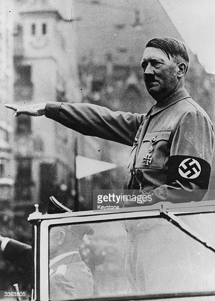Nazi dictator of Germany Adolf Hitler gives the nazi salute from his motorcade