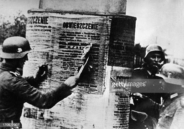 Nazi invasion of poland september 1939 german soldiers tearing down a polish proclamation world war 2