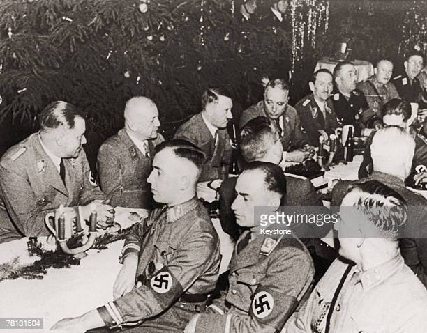 Nazi leader Adolf Hitler at a Christmas eve dinner with longserving party members at the Lion beer hall in Munich 24th December 1938 Back row left to...