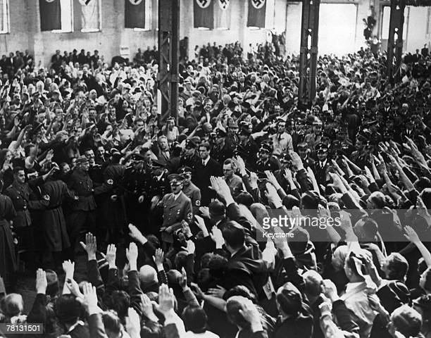 Nazi leader Adolf Hitler is welcomed by a 20000strong crowd giving the Nazi salute as he arrives at the Machine Hall in Graz Austria shortly after...
