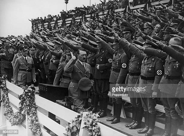 Nazi leader Adolf Hitler salutes the crowds at the Nuremberg Rally marking the 6th Party Congress of the Nazi Party, September 1934 .