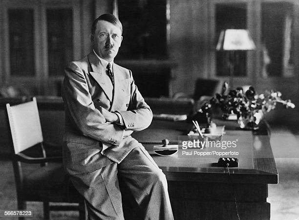 Nazi leader Adolf Hitler sitting on the edge of a desk at his Berghof residence Berchtesgaden Bavaria Germany during World War II circa 1940