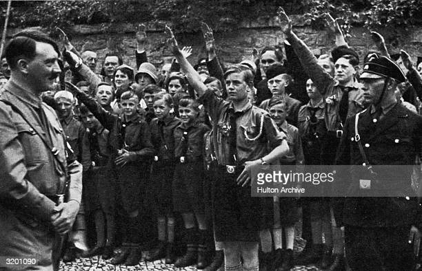 Nazi leader Adolf Hitler smiles while uniformed Saxon youths salute him outdoors in Erfurt Germany
