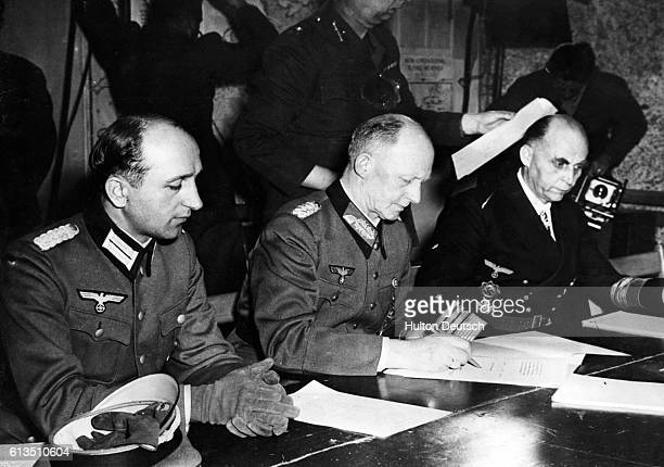 Nazi military officers Major Oxenius Wilhelm Colonel General Gustaf Jodl and General HansGeorge von Friedburg sit down to sign the unconditional...