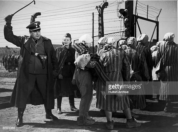 Nazi officer raises his riding crop as a group of women carry a fellow prisoner away in a scene from Wanda Jakubowska's 'Ostatni Etap' which was...