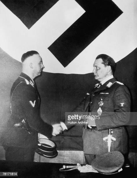 Nazi officials Heinrich Himmler and Hermann Goering shake hands beneath a swastika circa 1935