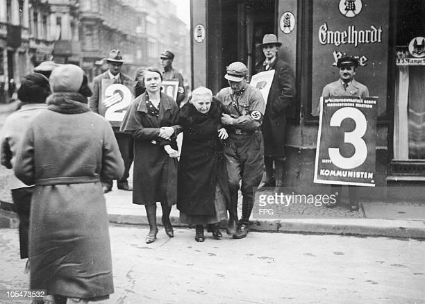 A Nazi Party member helps an elderly women from a polling station during the German federal election Berlin November 1932 On the right is a man...