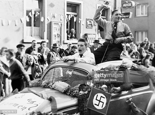 A Nazi Party member rides in the back of a Volkswagon automobile during a parade in Germany