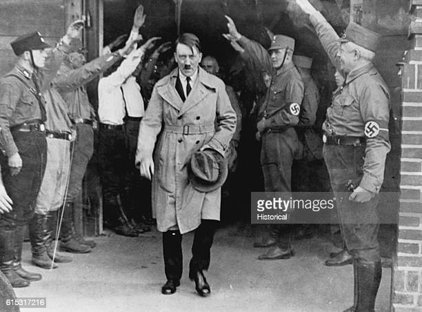 Nazi Party members salute German Chancellor Adolf Hitler as he emerges from a party meeting after a speech