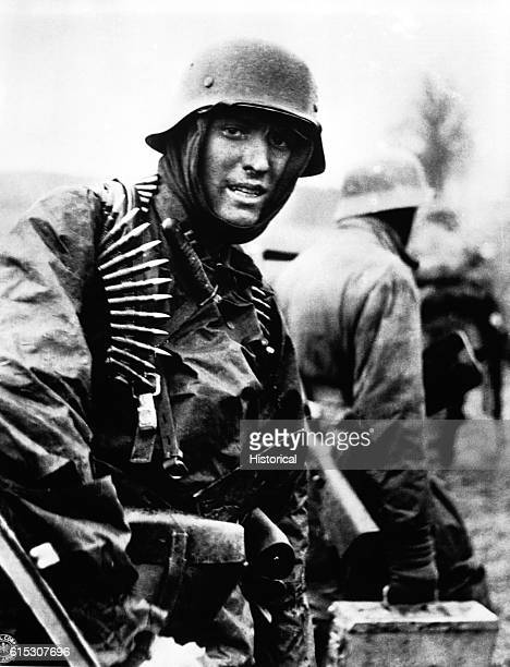 A Nazi soldier heavily armed carries ammunition boxes forward with companion in territory taken by their counteroffensive in this scene from captured...