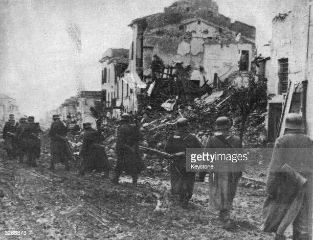Nazi soldiers march through a devastated town in the battle area of Italy. Along the whole of the 100-mile main Anzio front, the activity has been...