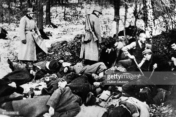 Nazi soldiers supervise as Polish prisoners dig a grave for fellow prisoners shot in a mass execution. When the task is done these prisoners will be...