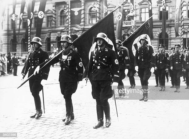 Nazi stormtroopers in Weimar carrying swastika flags in ceremonial dress