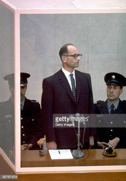 Nazi war criminal Adolph Eichmann stands in a protective glass booth flanked by Israeli police during his trial April 21 1961 in Jerusalem The...