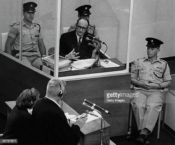 Nazi war criminal Adolph Eichmann stands in a protective glass booth flanked by Israeli police during his trial June 22 1961 in Jerusalem The Israeli...