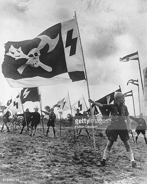 Nazi youths display flags in an open air camp near Berlin. From the sixth year of age, German boys have to join the Nazi organization of youth....