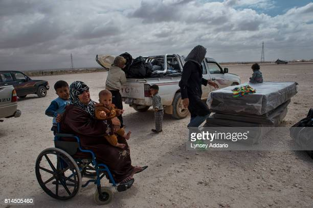 Nazira Toamah sits semiparalyzed from the waist down as her relative Mohammed Suleiman arranges their belongings the morning after arriving in the...