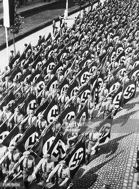 Nazis march through the streets of Nunberg to the Nazi Part Congress carrying flags adorned with swastikas which have just be adopted as the sole...