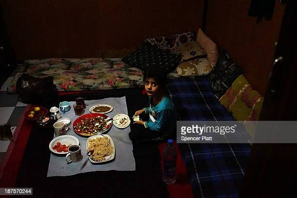Nazmiya a Syrian refugee from the city of Aleppo sits down for a meal inside the small room she shares with five people in a poor section of Beirut...